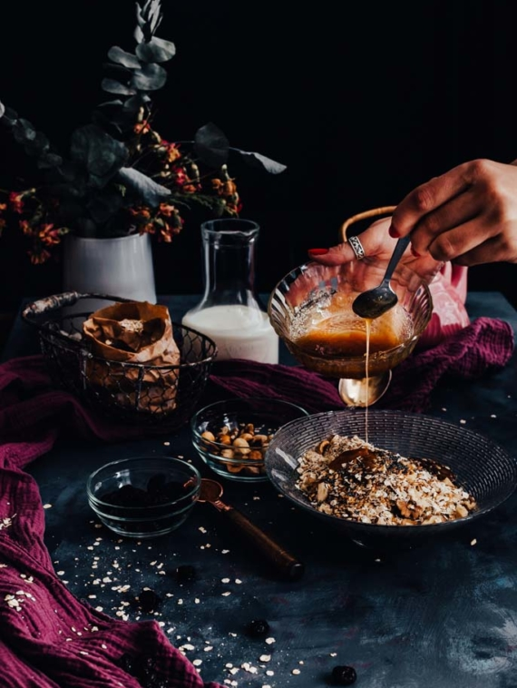 Woman hands drizzling honey on a granola bowl